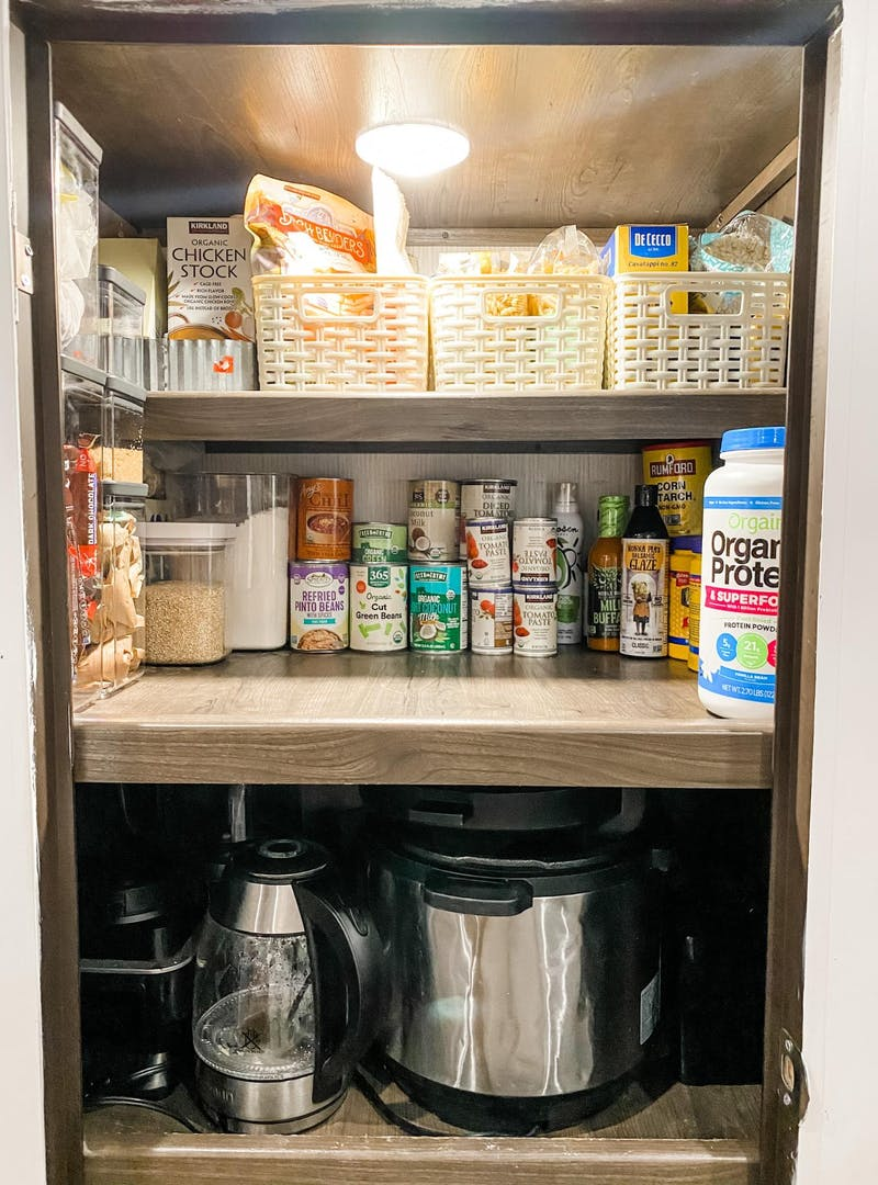 A shot of Brittnee Proha's pantry that is organized using pull out baskets to optimize storage in her Heartland Cyclone.