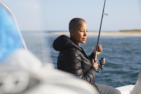 Sonya Lowery holding a fishing pole on a deep sea fishing trip in Cape Cod.