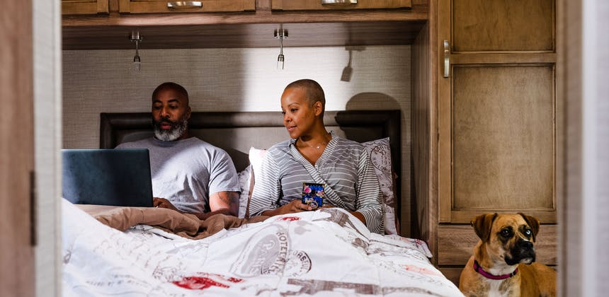Sonya Lowery and Ray Young relaxing in bed while working on the computer in their Jayco Redhawk.