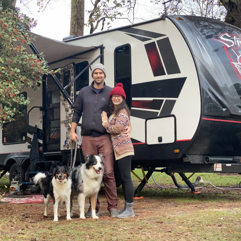 Amy Rekart and her husband pose with their two dogs in front of their Cruiser Stryker toy hauler.
