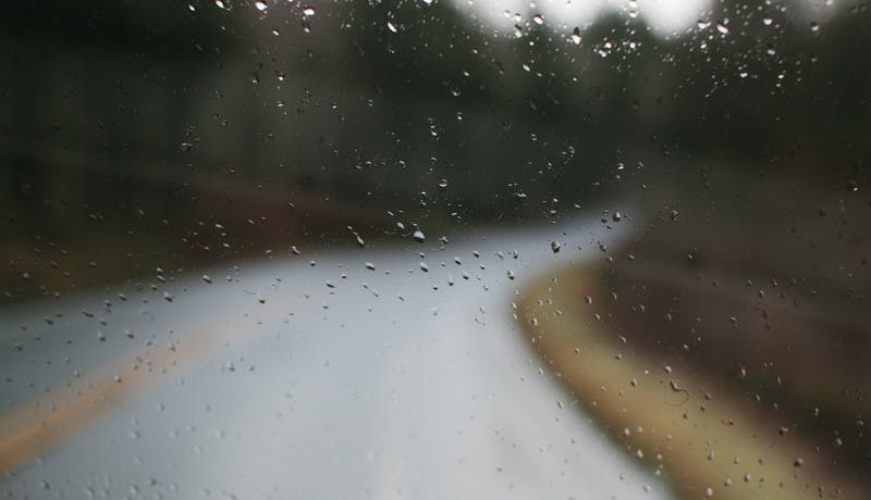 Water droplets on an RV window with a blurry road in the background.