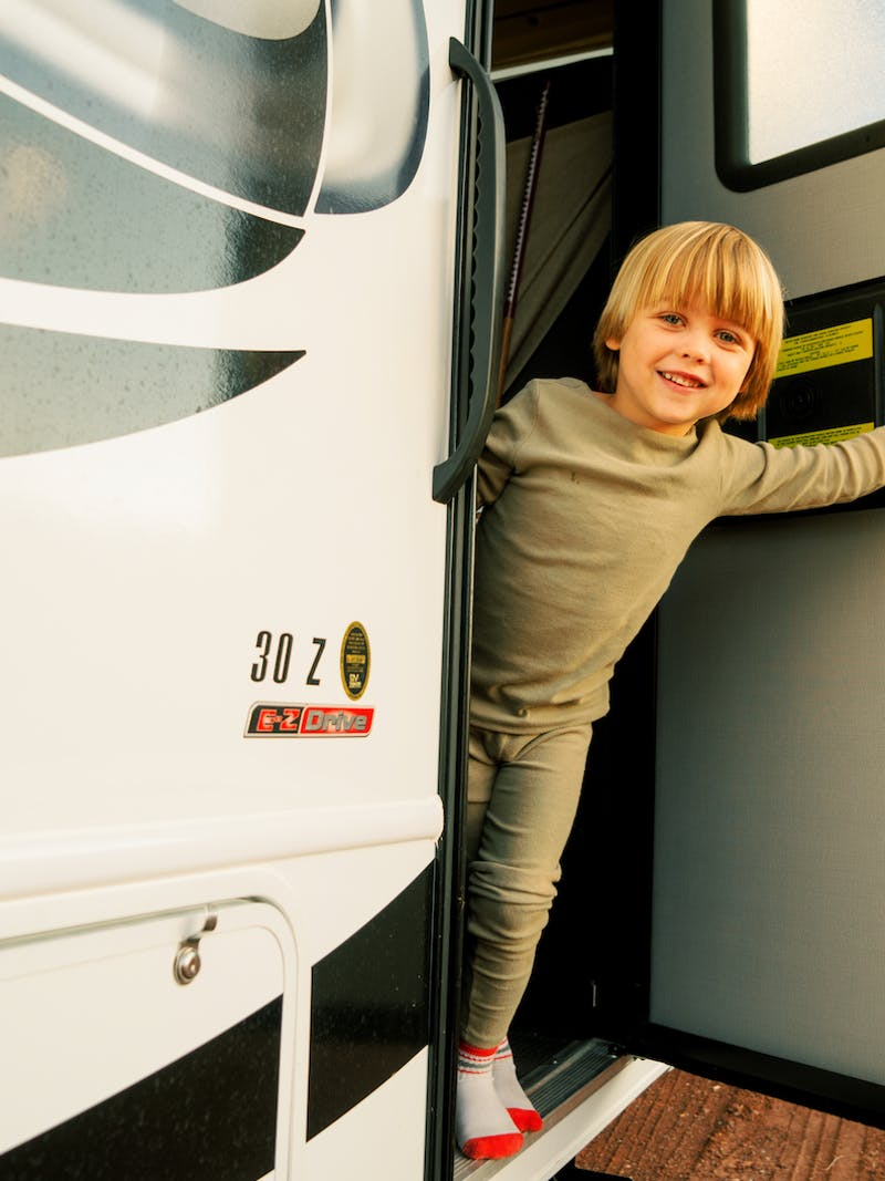 Little boy opens front door of Thor Class C motorhome and smiles out at the camera