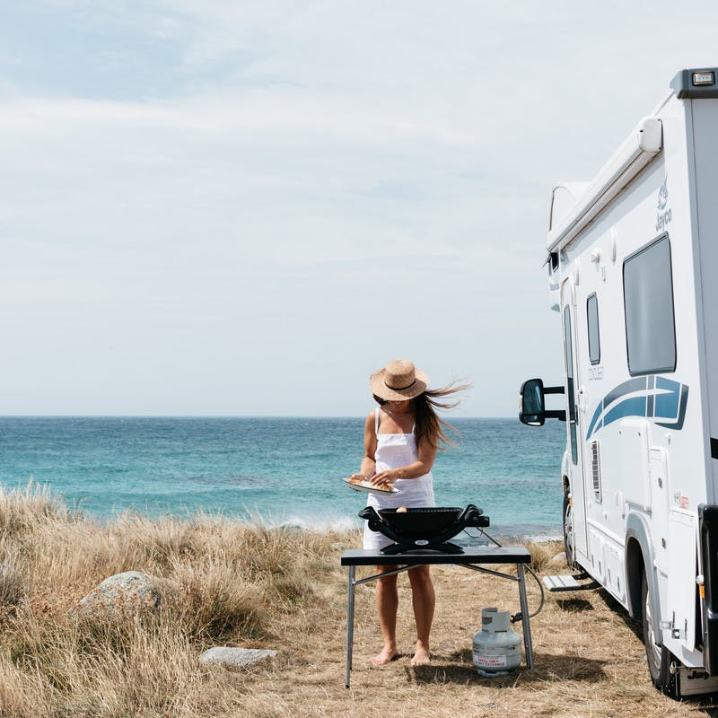 Sarah Glover cooking on a table by the ocean next to Class C motorhome.