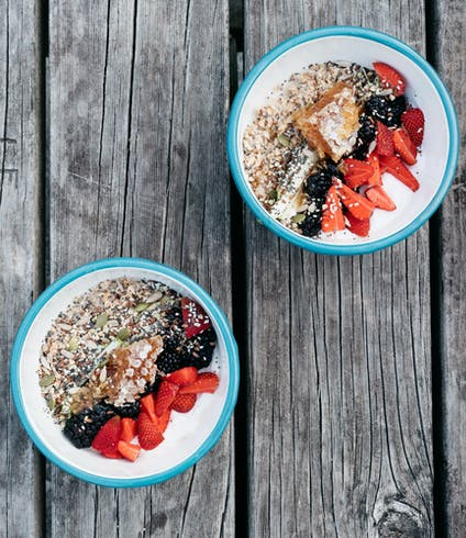 Two  bowls of overnight oats topped with berries on a weathered picnic table.