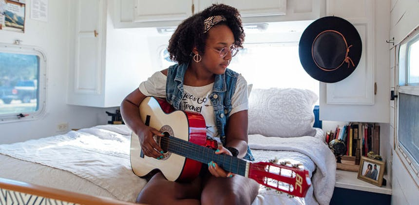A teenage girl practicing the guitar.