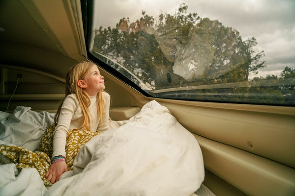 A young girl looks out the window of an RV at the view.