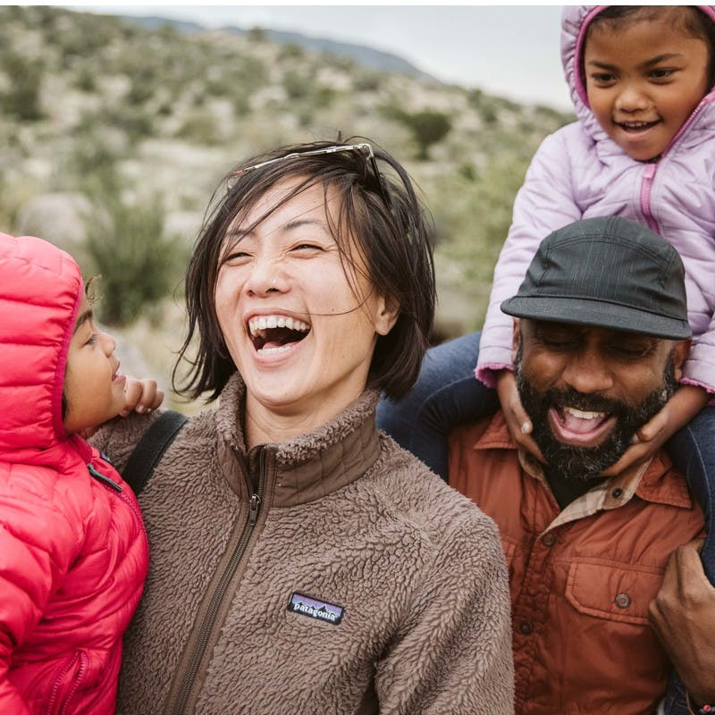 Close up of laughing family, Asian American woman and African American man, with two kids in puffy jackets and hoods.