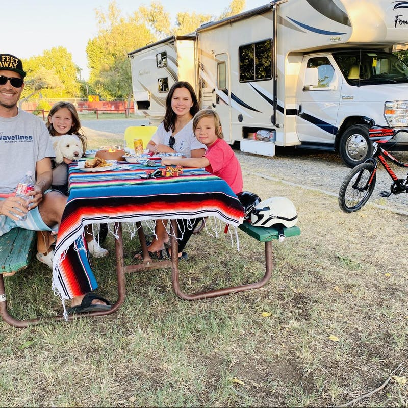 Raoul Martinez and his family sit by a picnic table in front of a Thor Motor Coach Four Winds Class C RV.