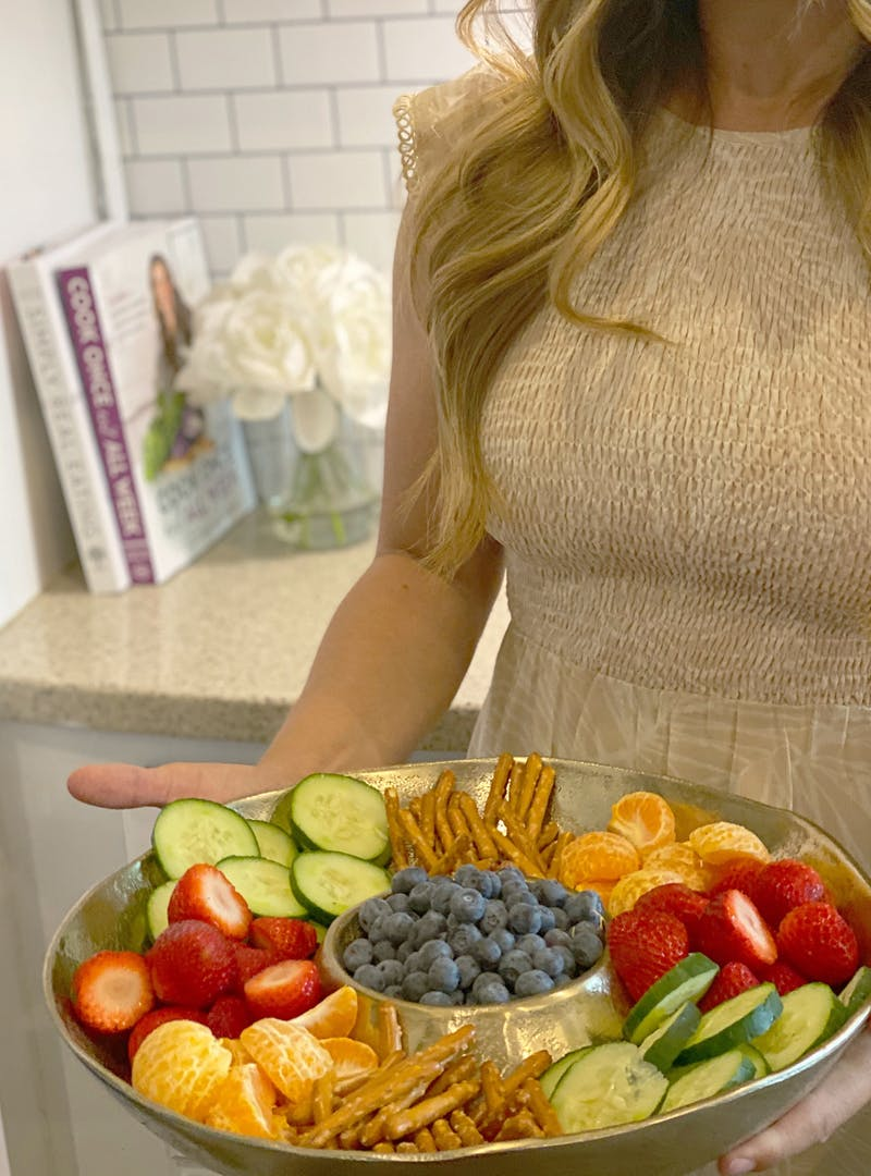 A tray of healthy bedtime snacks, including oranges, strawberries, cucumbers and pretzels.