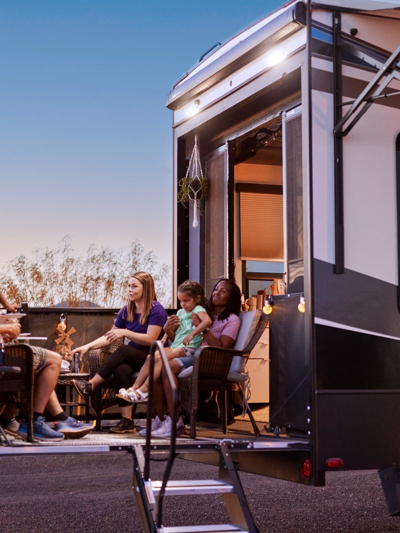 Robin and Warren's family sit on the patio of their Keystone Fuzion at dusk.