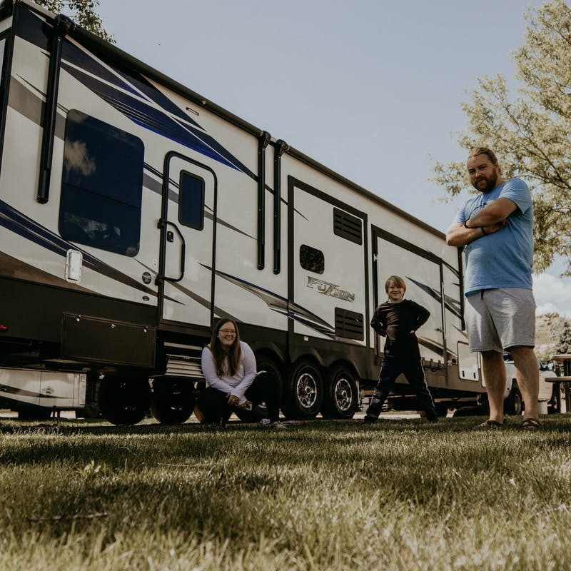 A family standing outside their Toy Hauler RV in the grass.
