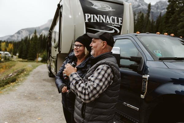 Tina and Craig Klinefelter standing outside their RV with binoculars, looking for wildlife.