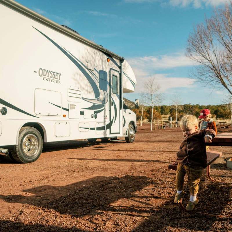 Two young boys sit at picnic table at dirt campsite in front of Thor class c motorhome