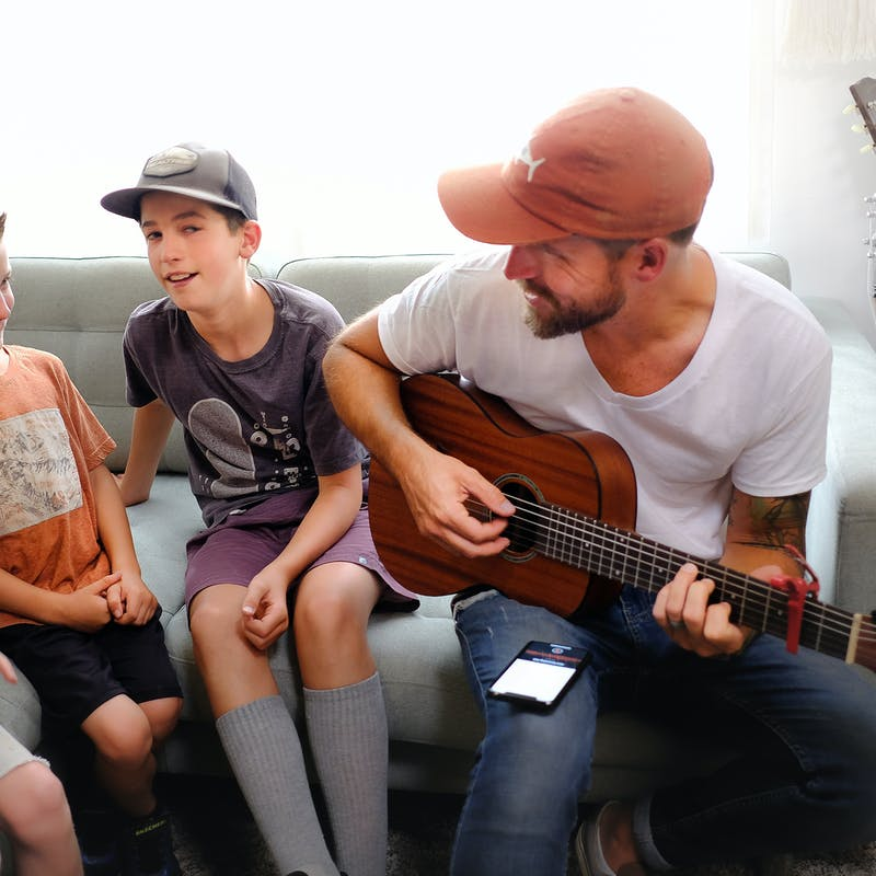 Amick Cutler plays guitar while his three sons sing along while sitting on a couch in their RV.