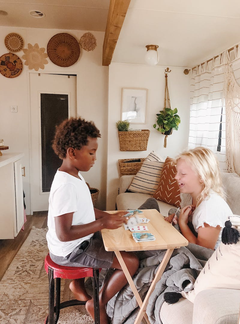 Shannon Carew's children play card games together inside their Highland Ridge RV.