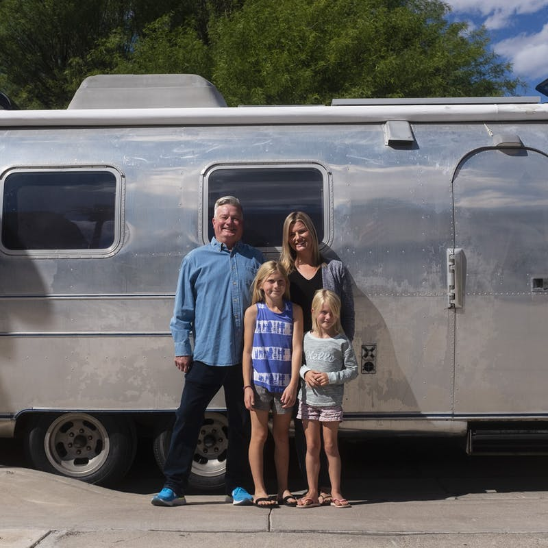 Bill Hartig with his daughter and two grand-daughters, posed in front of their family RV.