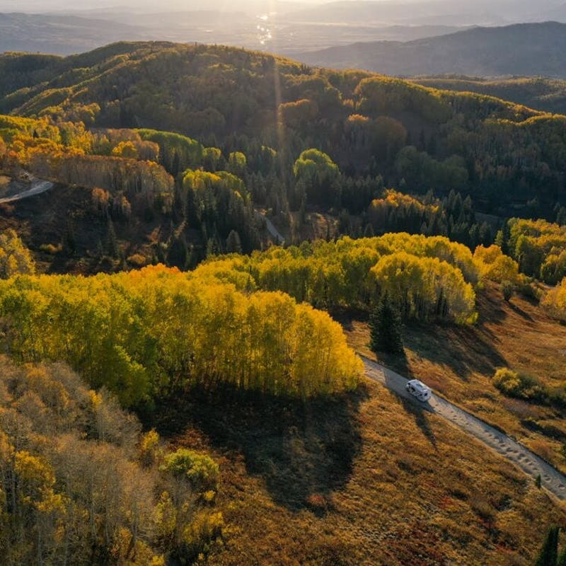 Drone shot of a Class C RV driving through golden hills and yellow trees