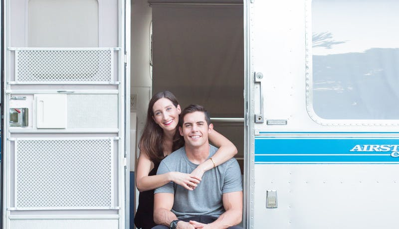 Christina and Mack Griffin posed in the doorway of their Airstream RV.