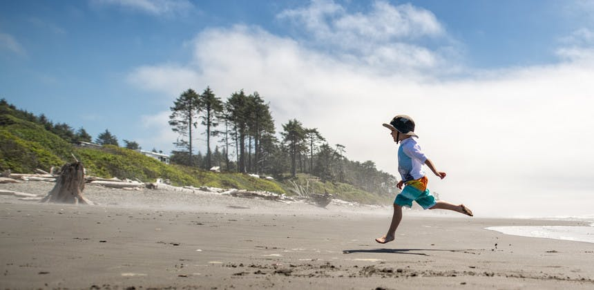 Young boy jumping and skipping on ocean beach with trees in the background
