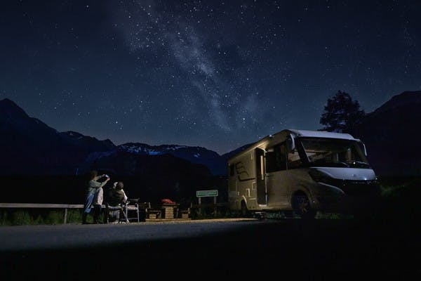 Family stargazes in the mountains of Austria next to their Class B RV from Hymer.
