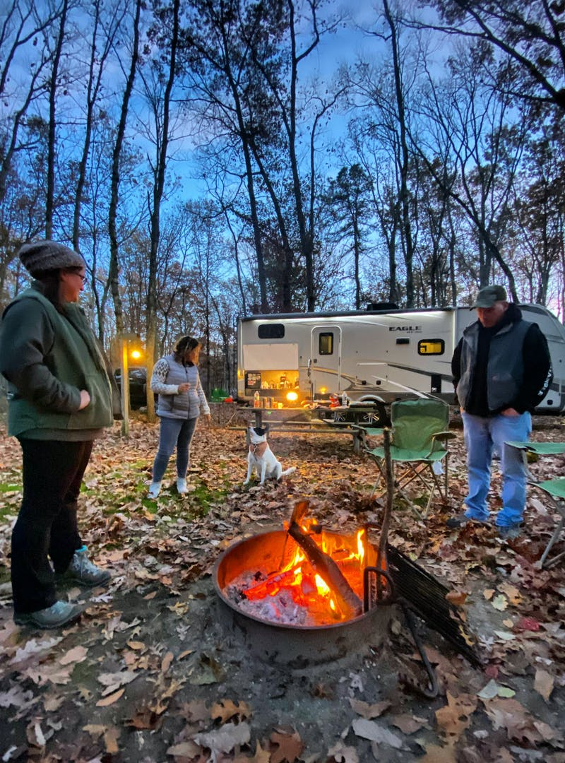 Three adults around a campsite fire pit, social distancing.