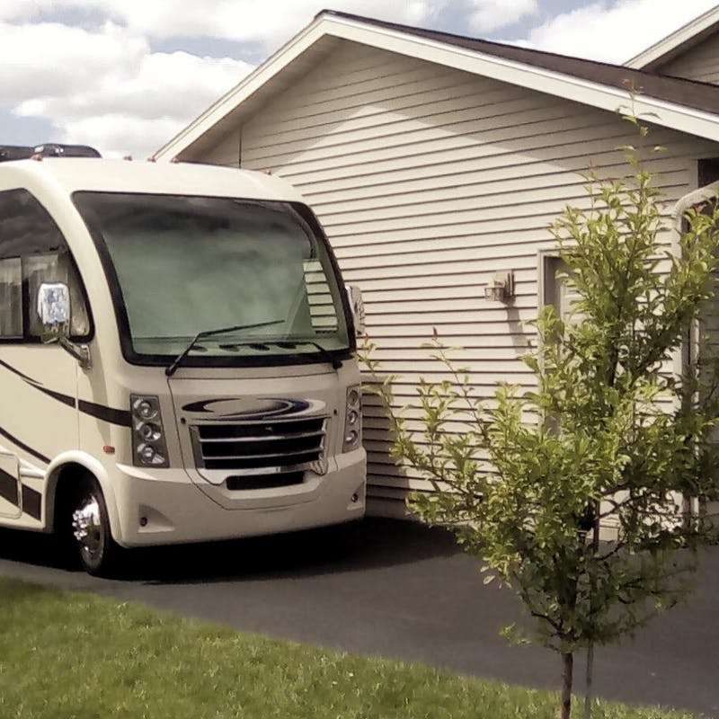 A Thor RV parked in a driveway next to the Bolands' house.