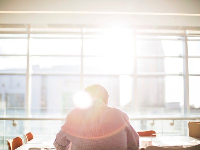 man sits alone at a table by window with sun streaming in