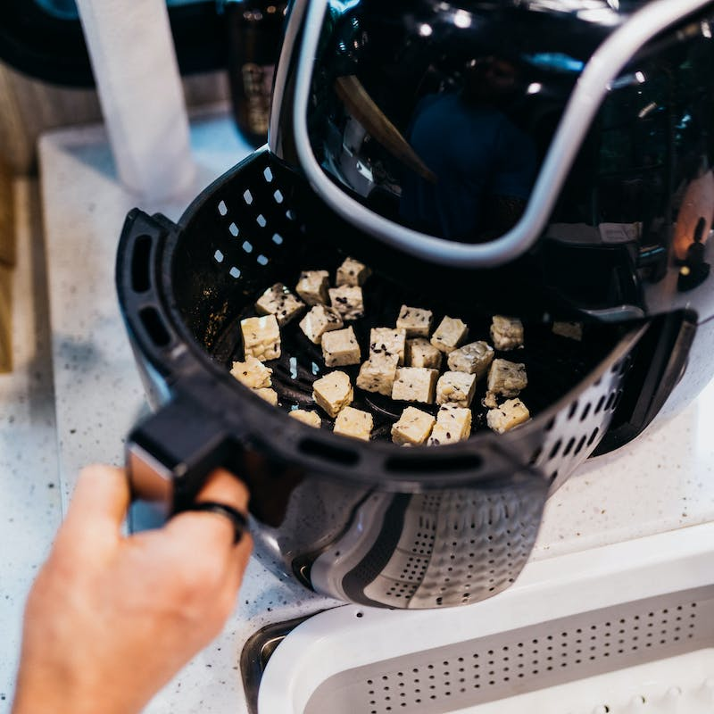Crispy tofu cubes in the basket of an air fryer.