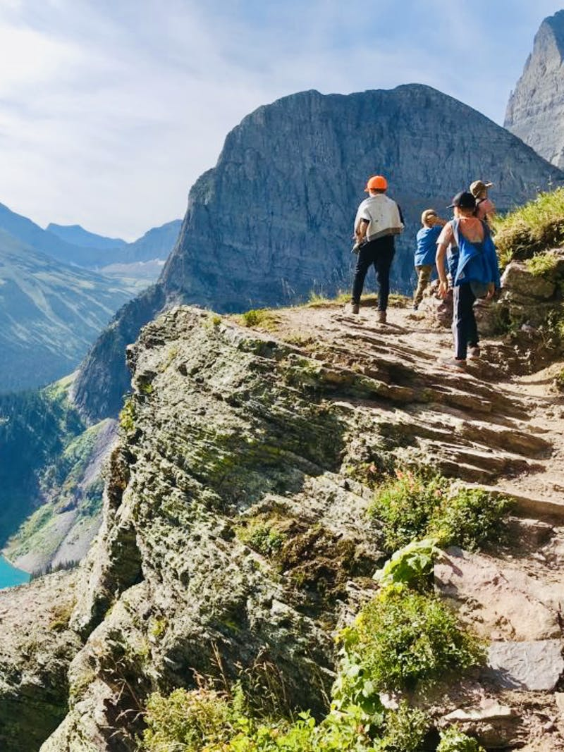 A family hiking a rocky path in idyllic Glacier National Park.