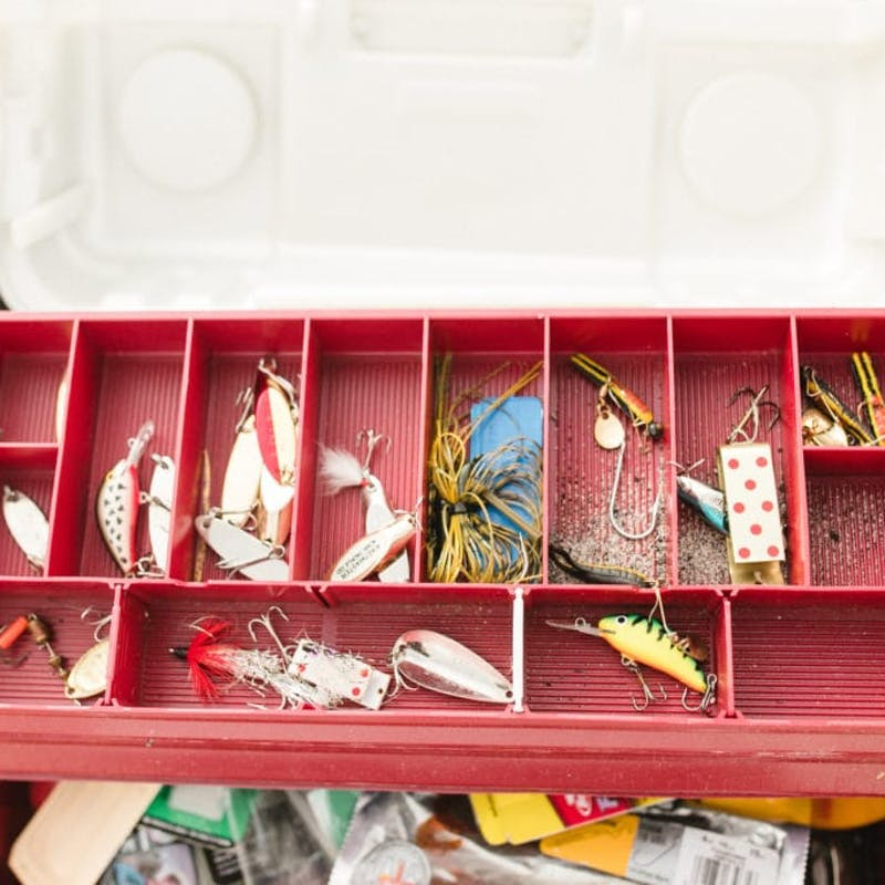 Red tackle box open and full of hooks and bait