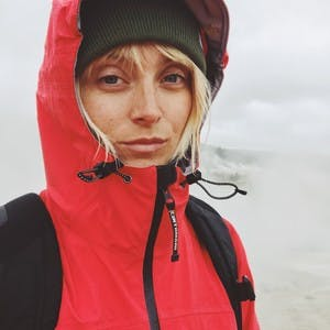 Laura Jayne Austin, wearing a beanie and a red jacket with her hood up, slightly smiles at the camera.