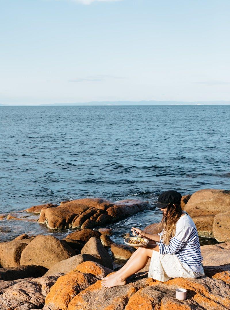 Sarah Glover in a black hat, sitting on orange rocks by the ocean, eating breakfast.