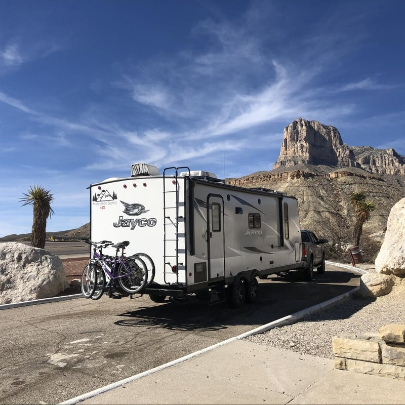 Ben and Christina McMillan's Jayco Jay Feather driving down the road near large rocks traveling from Texas to New Mexico.