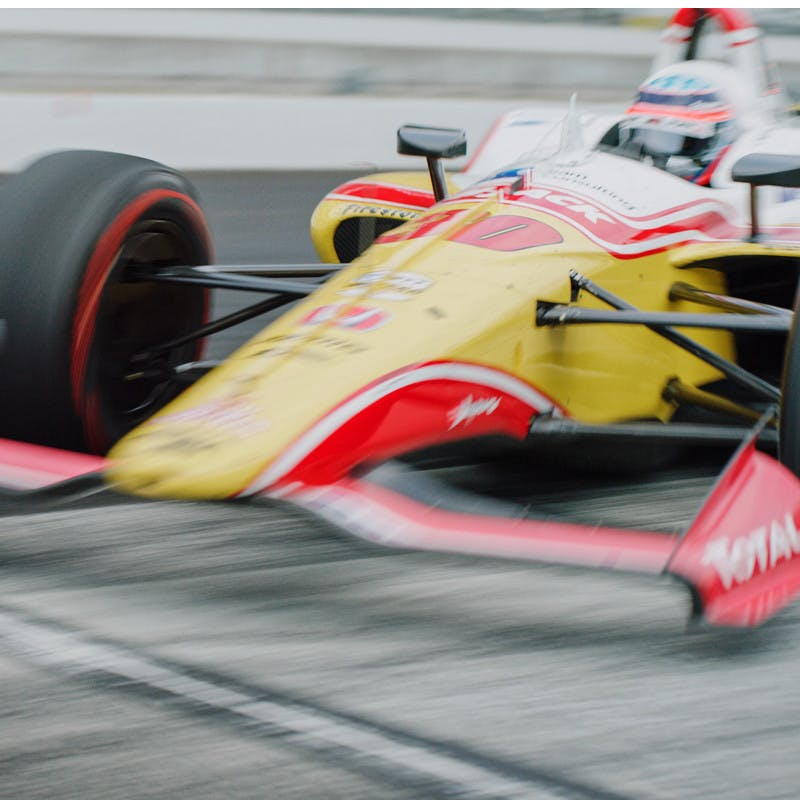 Takums Sato's race car zooms down the track at the Indy 500.