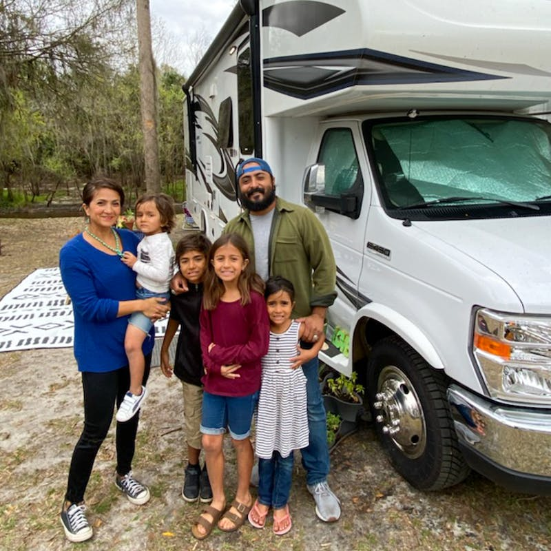 Sandra Peña's family of six poses for a photo in front of their Jayco Class C RV.