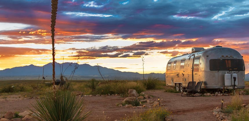 An Airstream trailer parked under a rainbow sunset in the desert.