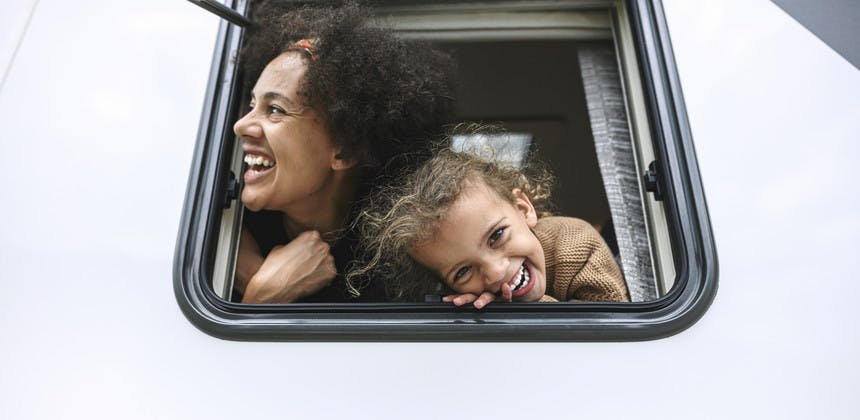 Mother and daughter laughing and smiling putting heads out of rv window