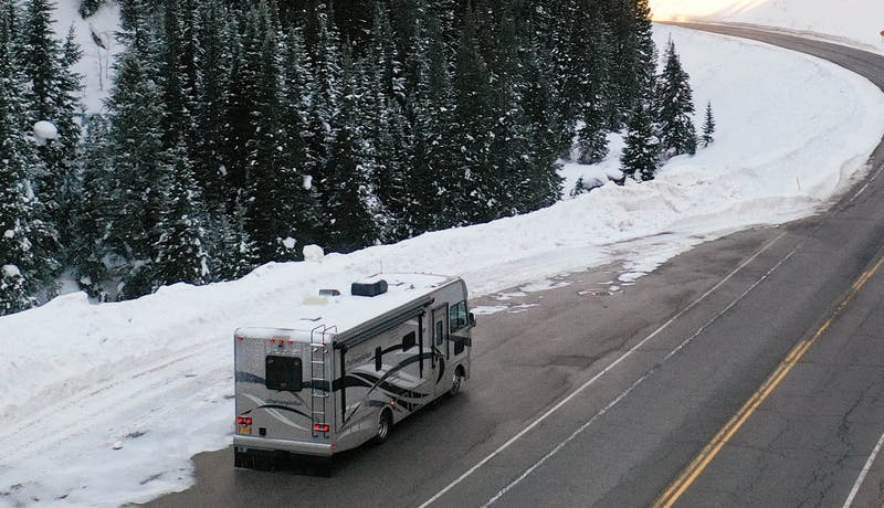 An RV driving up a mountain in golden light.