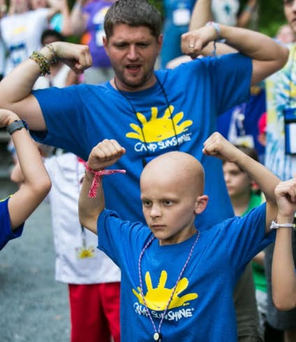 A child poses to show off his muscles at a KOA Care Camp event.