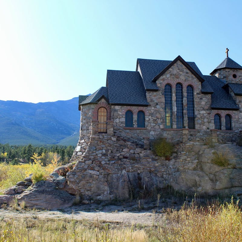 Stone church in the middle of a grassy field surrounded by mountains