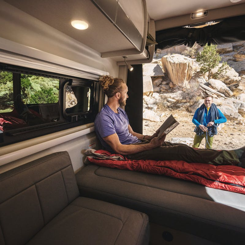 A man sits on the bed of a Class B RV