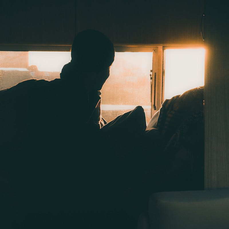 Early morning sun shines in an RV window onto a person still in bed.