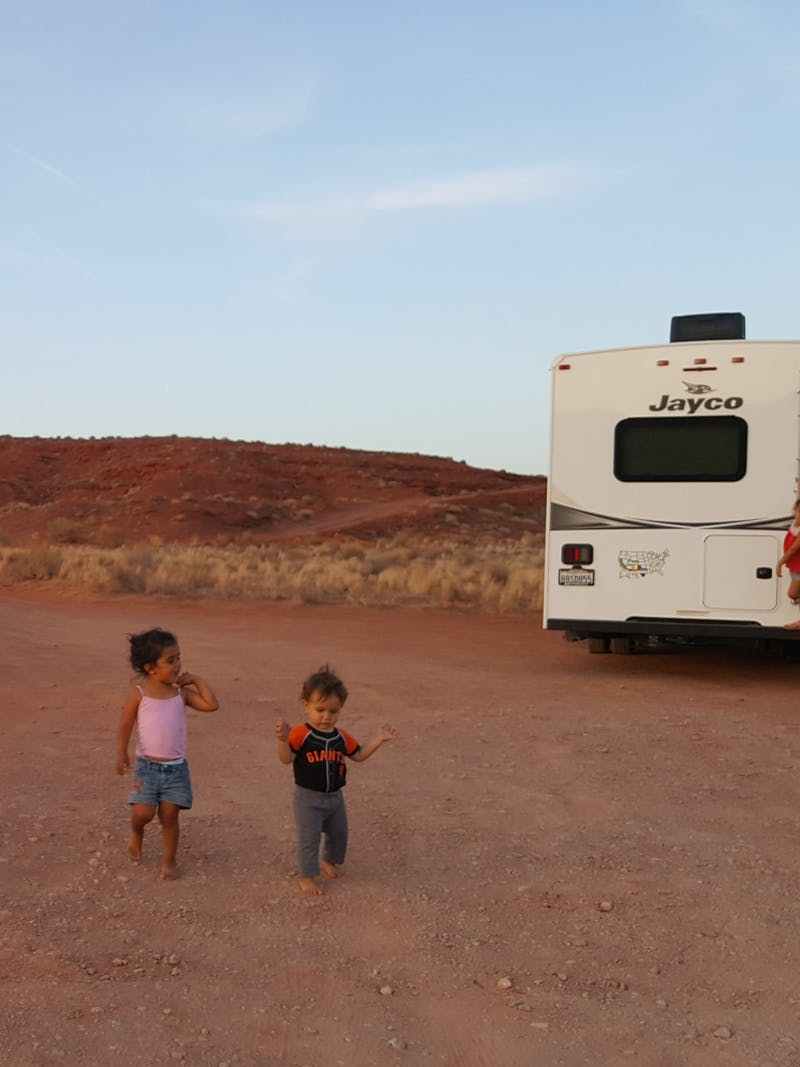 Sandra Peña's kids run around outside on a dirt road in front of her Jayco Class C RV.
