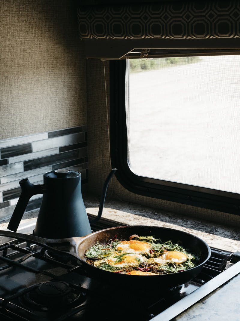 Skillet filled with swiss chard and pesto shakshuka in the RV kitchen.