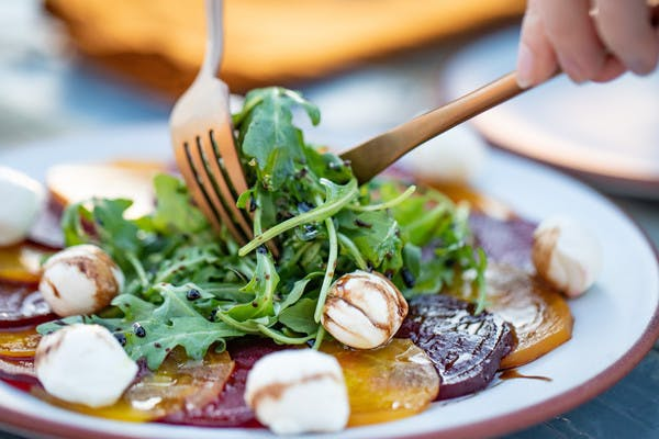Close up of gold and red beats, topped with arugula, mozzarella cheese balls, and drizzled with a balsamic dressing, includes a knife and fork.