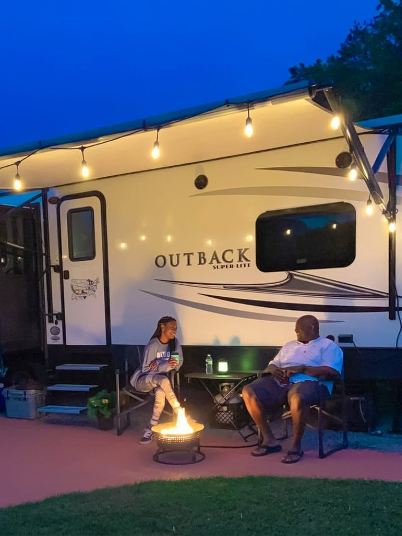 A couple sits in front of their Keystone Outback RV by a campfire at night