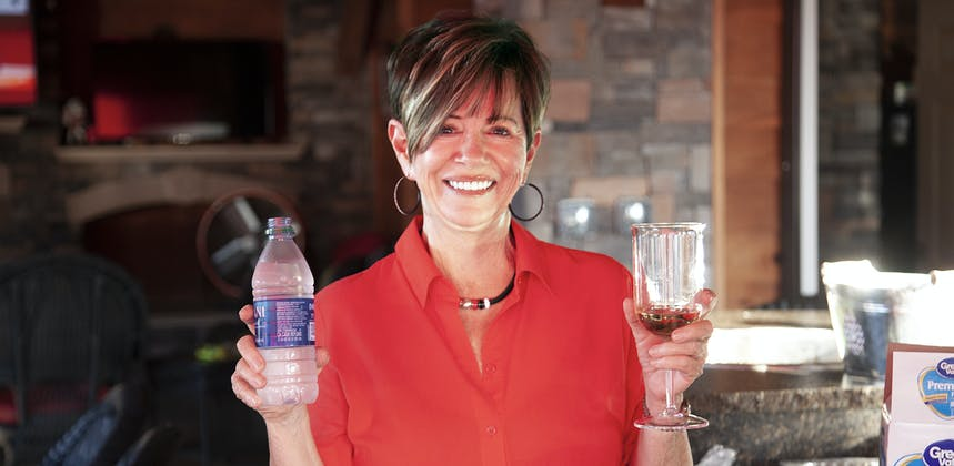 A woman holding an alcoholic beverage in one hand and a bottle of water in the other, on display for the camera.