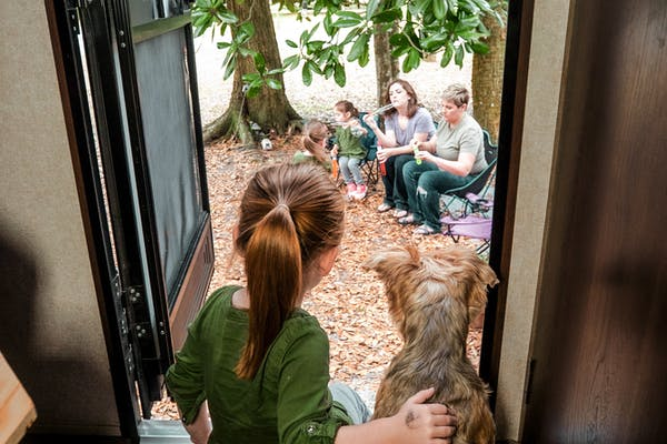 A little girl sits with a dog in an RV doorway, looking outside at her parents and sisters.