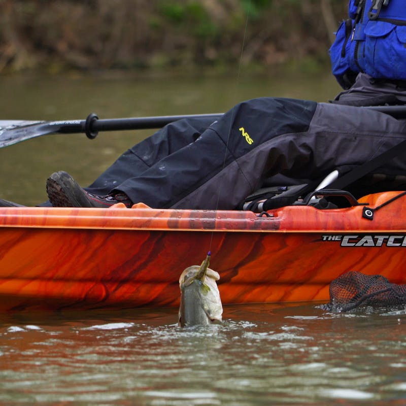Pulling a fish out of the water from a red kayak.