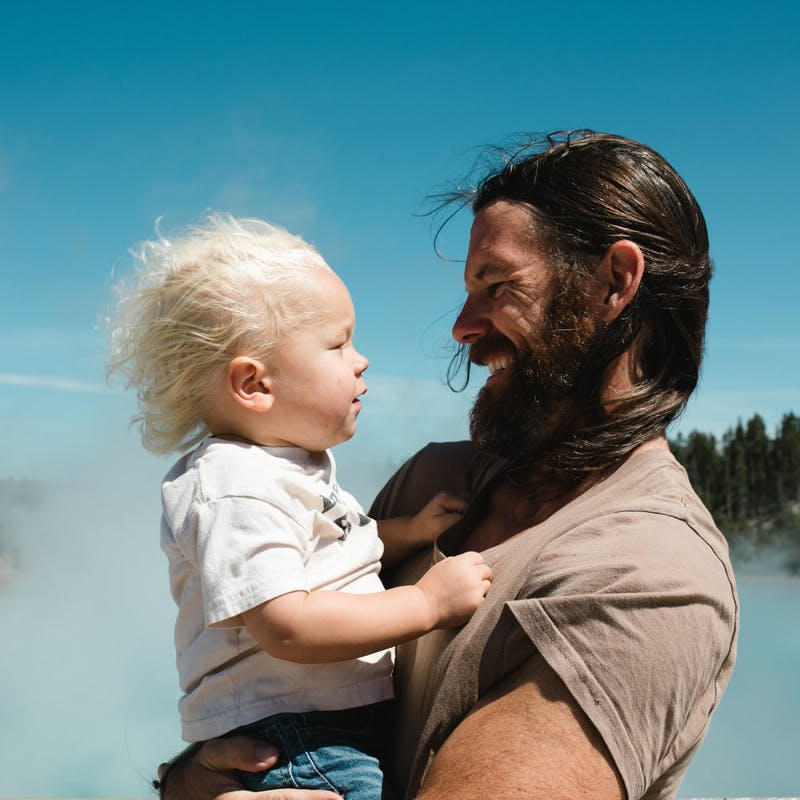 Father holds son and looks at each other in front of steaming hot springs